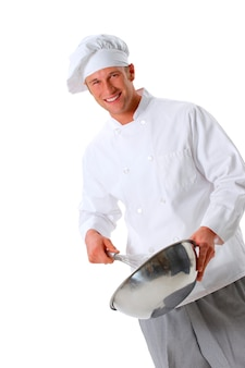 Chef in chef's whites and toque holding whisk and bowl mixing batter
