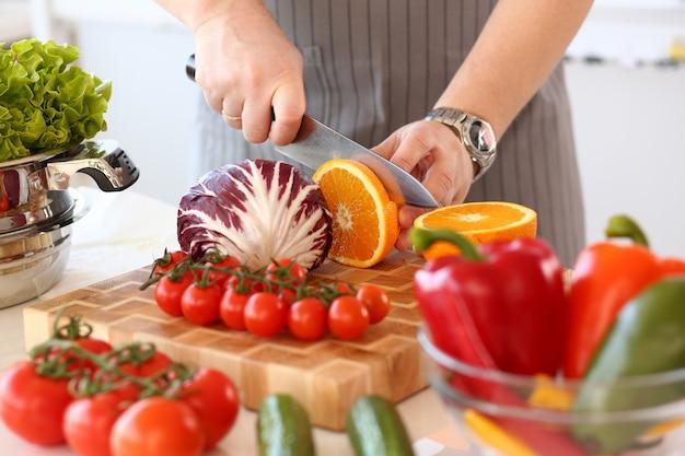 シェフチョップジューシーオレンジフルーツキッチン写真。手にナイフでビーガンカット柑橘類。サラダ用の健康野菜成分。フレッシュトマト、キャベツ、コショウのボウル。料理ブログのクローズアップショット