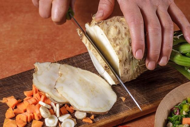 シェフがキッチンボードで野菜を刻んで
