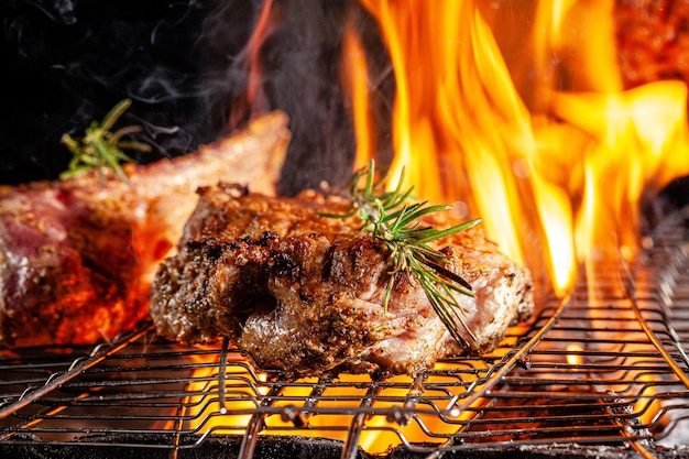 Chef cook fries meat, beef steak on an open fire in a restaurant