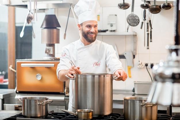 Шеф-повар в униформе готовит суп в большой плите на кухне ресторана