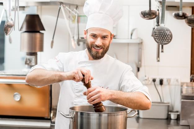Шеф-повар в мундире с перцем в большой плите на кухне ресторана