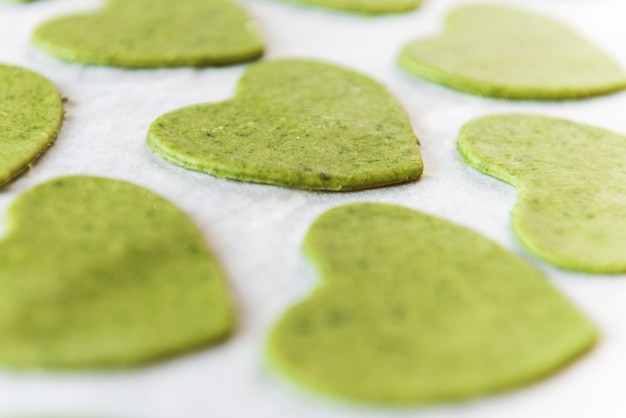 シェフの料理人が一歩一歩、お祝いのディナーのためにハートの形をした緑のラビオリを作ります