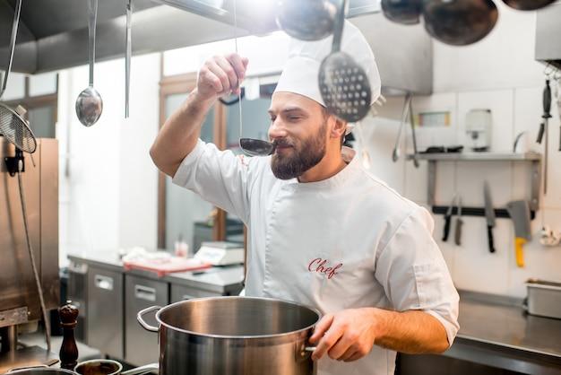 Шеф-повар готовит дегустацию еды с большой ложкой на кухне ресторана