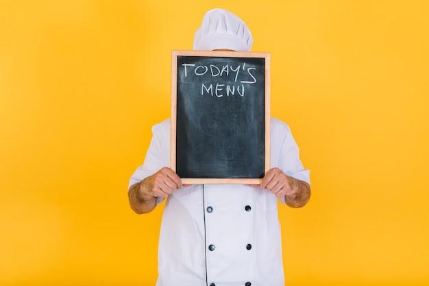 白いキッチンの帽子とジャケットを着た料理人シェフが、黄色の背景に「今日のメニュー」と書かれた黒板で顔を覆っています。