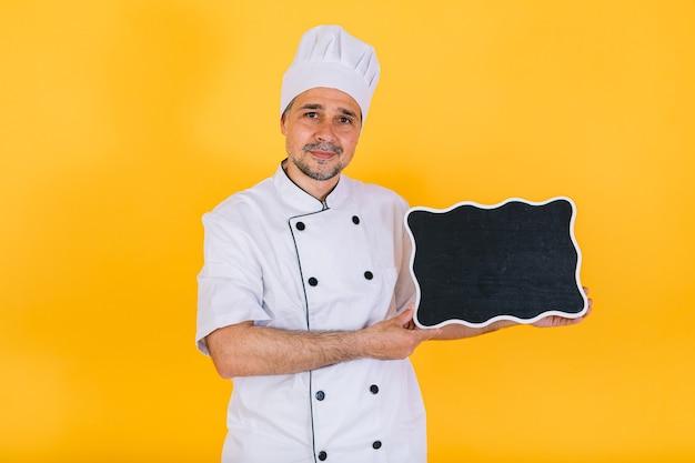黄色の背景に、白いキッチンキャップと黒い黒板を保持しているジャケットを着てシェフの料理人