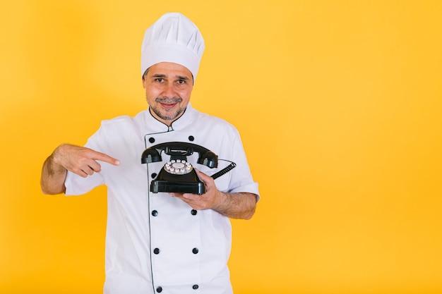 黄色の背景に、レトロな電話を持って指している白いキッチンキャップとジャケットを着てシェフの料理人