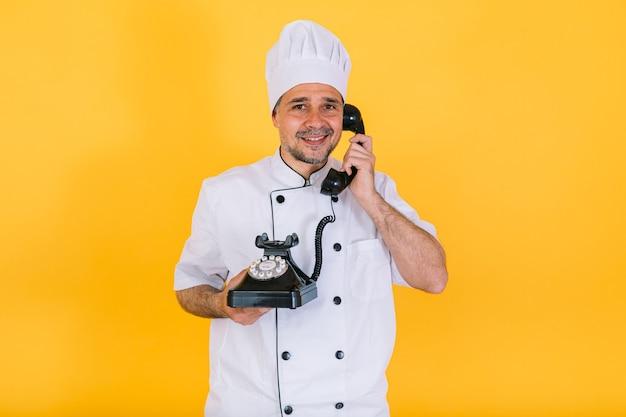 白いキッチンキャップとジャケットを着たシェフの料理人が、黄色の背景にレトロな電話で話します