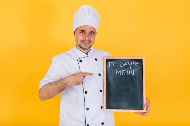 黄色の背景に「今日のメニュー」と書かれた黒板を持った白いキッチン帽子とジャケットを着た料理人