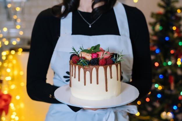 シェフクッカーがフルーツ入りの自家製クリスマスケーキを持っています。明けましておめでとうございます。