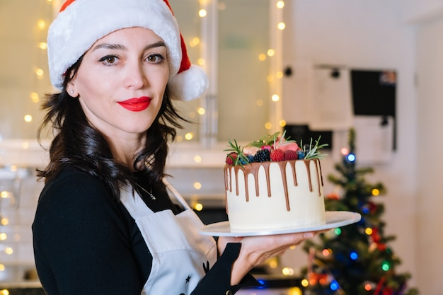 Chef-cooker is holding homemade christmas cake with fruit. happy new year and merry christmas