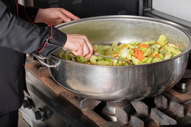業務用厨房で料理をするシェフ