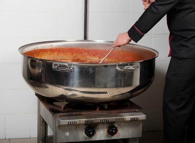 Шеф-повар готовит фасоль на коммерческой кухне Premium Фотографии