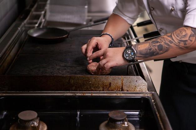 Шеф-повар готовит гамбургер на гриль-ресторане. квалифицированный повар