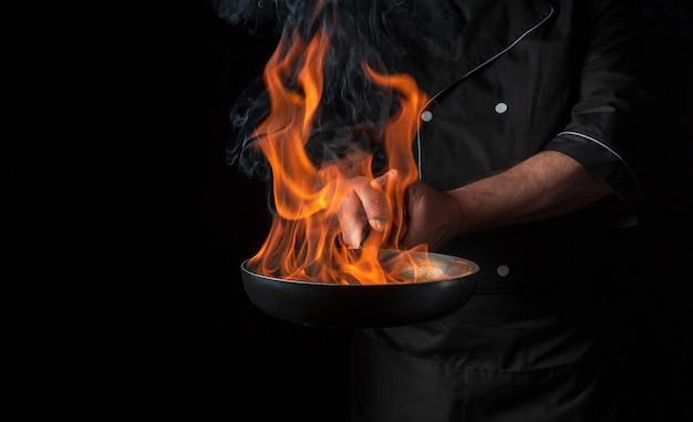 요리사는 검은 배경에 불을 붙이고 냄비에 음식을 요리합니다. 레스토랑 및 호텔 서비스 개념입니다. 무료 광고 공간