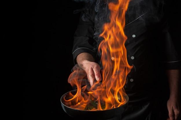 검은 배경 레스토랑 및 호텔 서비스 개념에 불을 붙인 팬에 요리하는 요리사