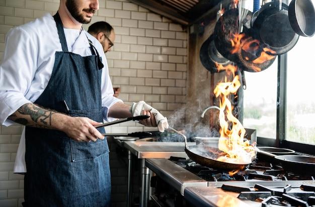 레스토랑 주방에서 음식을 요리하는 요리사