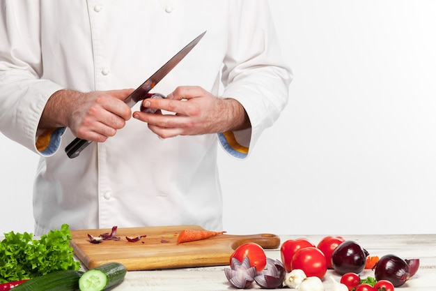 Шеф-повар готовит салат из свежих овощей на своей кухне