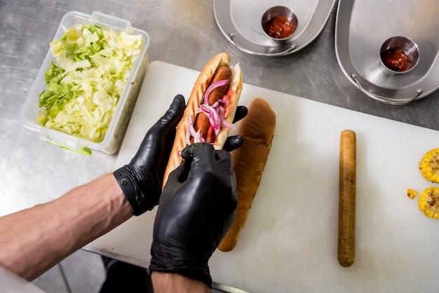 Шеф-повар готовит хот-дог на гриле. ресторан.