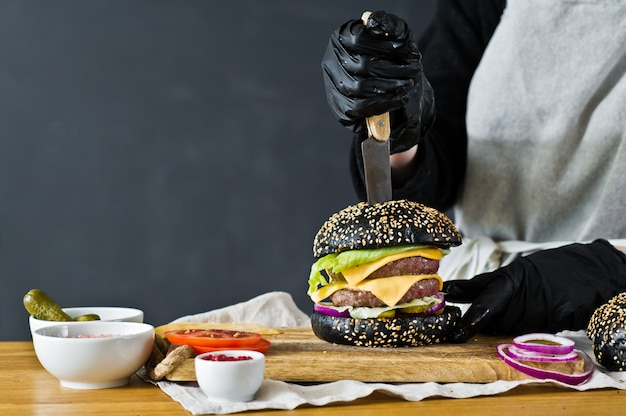 The chef cooking a juicy burger. the concept of cooking black cheeseburger. homemade hamburger recipe.