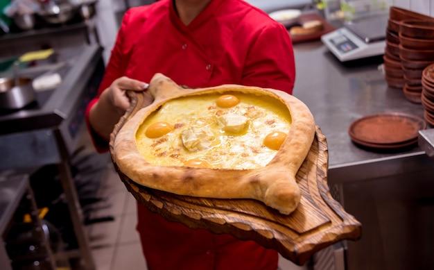 シェフがチーズと卵でハチャプリを調理します。グルジアの郷土料理。飲食店。