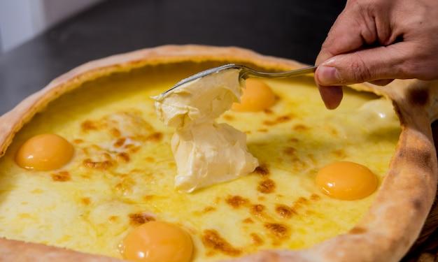 シェフがチーズと卵でハチャプリを調理します。グルジアの郷土料理。