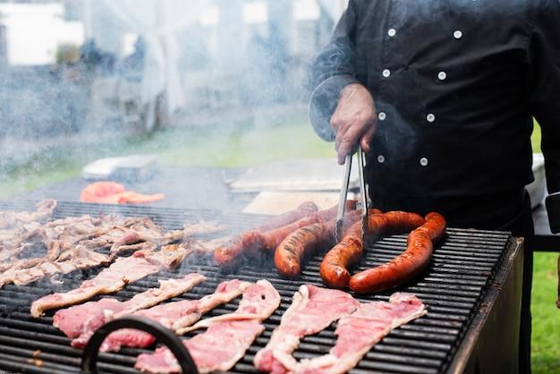 Шеф-повар готовит мясо на пеллетном гриле-коптильне