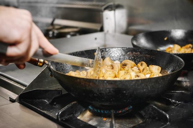 Шеф-повар готовит грибы на сковороде на горящем огне