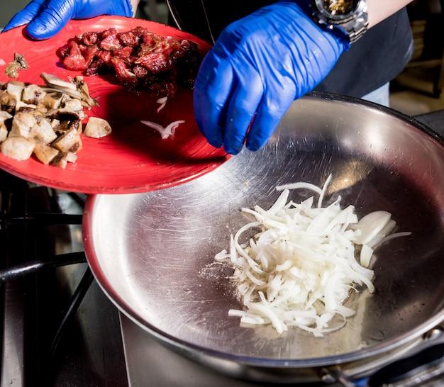 鍋に肉とパスタを調理するシェフ。イタリアンスタイルの料理。飲食店。