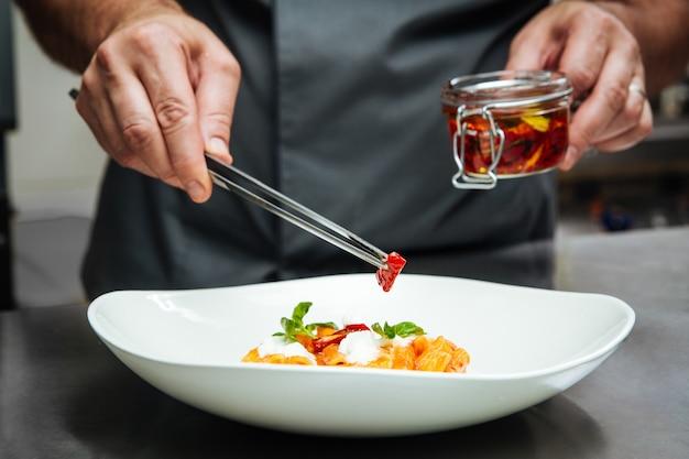 흰색 접시에 sundried 토마토와 펜 네 파스타를 요리하는 요리사