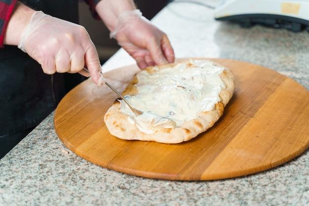 Chef cooking pinsa romana with pear, cheese, prosciutto. scrocchiarella gourmet italian cuisine.