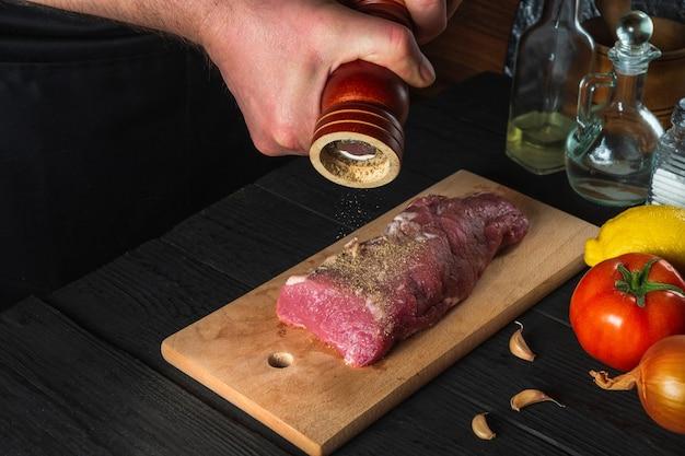 요리사는 생고기 필레를 요리하고 검은 배경에 마리네이드를 위해 후추와 칠리를 추가합니다. 레스토랑이나 카페의 주방 작업 환경