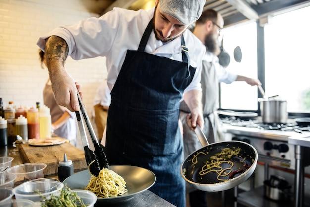 キッチンでスパゲッティを調理するシェフ