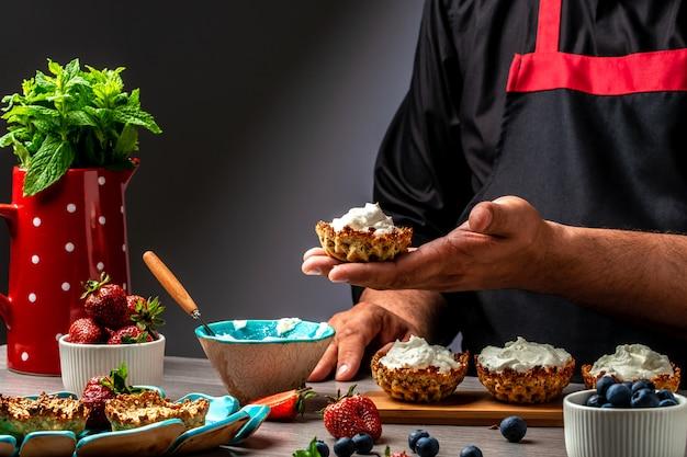 Шеф-повар готовит пироги со сливками, клубникой и черникой