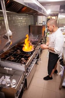 彼のレストランのキッチンで炎で調理するシェフ。熟練した料理人