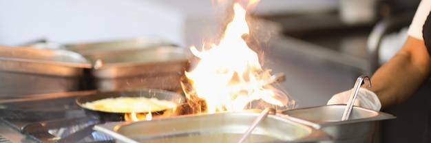 キッチンストーブのクローズアップで炎で調理するシェフ
