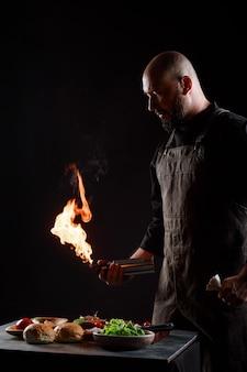 Шеф-повар готовит бургеры, жарит котлеты на открытом огне.