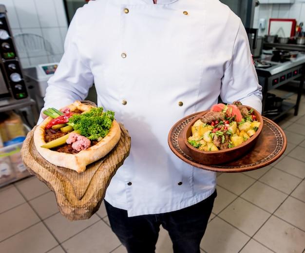 Шеф-повар готовит жареную картошку с кусочками мяса на кухне ресторана