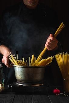 요리사는 야채 배경에 이탈리아 파스타를 요리