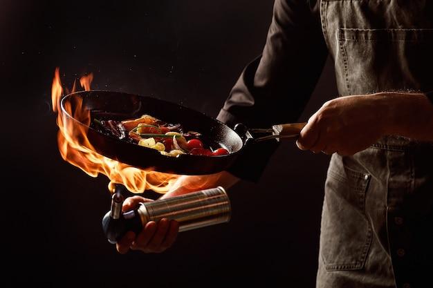Шеф-повар готовит с огнем на сковороде креветки с овощами