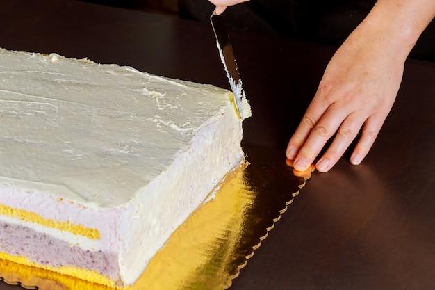 白いアイシングのお祝いケーキでシェフのカバー。レイヤースポンジケーキを作る。