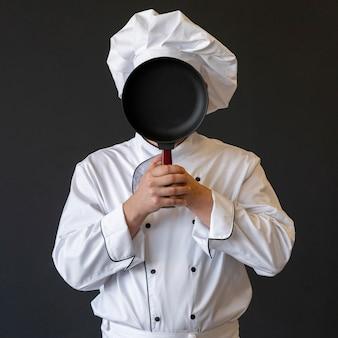 鍋で顔を覆うシェフ
