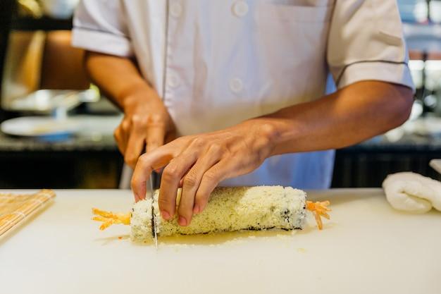 シェフがローリング巻き寿司をご飯、エビの天ぷら、アボカド、チーズで切りました。