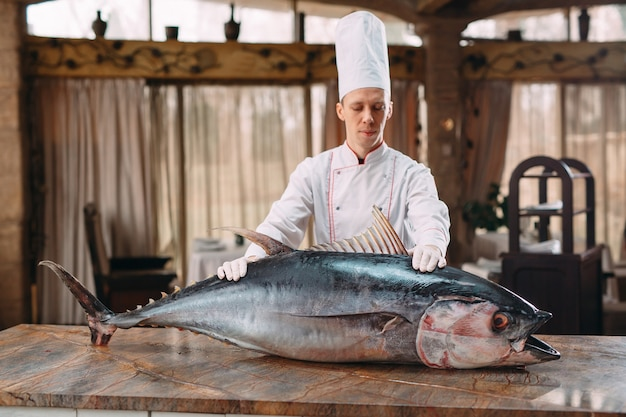 The chef cut up a big tuna fish in the restaurant.