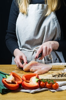 The chef cuts chicken breasts on a wooden chopping board.