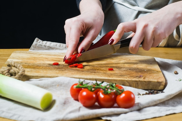 The chef cuts chili peppers on a wooden chopping board.