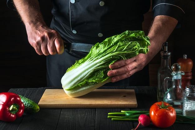요리사는 신선한 야채와 함께 빈티지 식탁에 샐러드용 칼로 신선한 나파 양배추를 자른다. 요리 및 레스토랑 또는 카페 개념