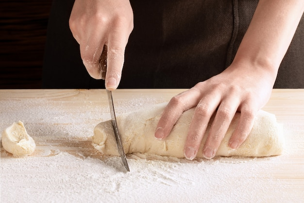 Chef cuts a piece of dough from a whole dough with a knife on a wooden table sprinkled with flour