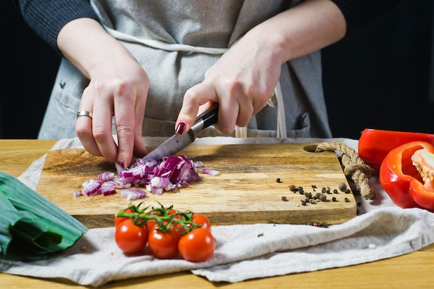 The chef cuts red onions on a wooden chopping board.