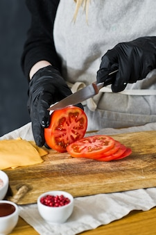 Chef cuts red tomatoes. the concept of cooking a black burger.
